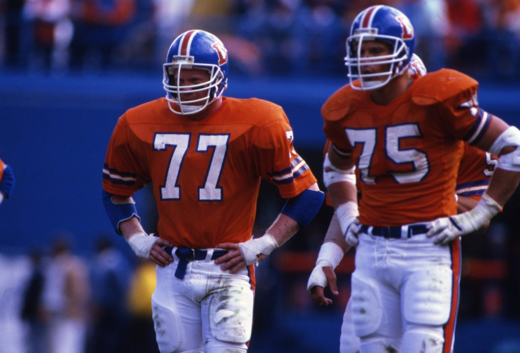 Denver Broncos linebacker Karl Mecklenburg and defensive end Rulon Jones (75) await the Dallas Cowboys offense during an NFL game in Denver, Oct. 5, 1986. The Broncos defeated the Cowboys 29-14. (AP Photo/Eric Lars Bakke)
