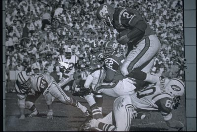 Fullback Cookie Gilchrist leaps over a Jets tackler as center Ray Kubala during an October 3, 1965 win (16-13) at Bears Stadium in Denver.