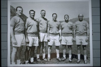 "The 1965 coaching staff: left to right, Director of Player Personnel Fred Gehrke, Offensive Backfield Coach Bus Mertes, Head Coach Mac Speedie, Offensive Line Coach Bob ""Red"" Miller, Defensive Line Coach Ray Malavasi, Defensive Backfield Coach George Dickson."