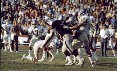 Los Angeles Raiders defensive end Lyle Alzado (77) pressures Denver Broncos quarterback Gary Kubiak (8)