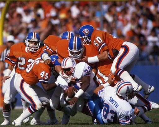 The Denver Broncos defense gang tackle Houston Oilers running back Stanley Edwards (32) during an NFL game in Denver, Colo., Oct. 5, 1985