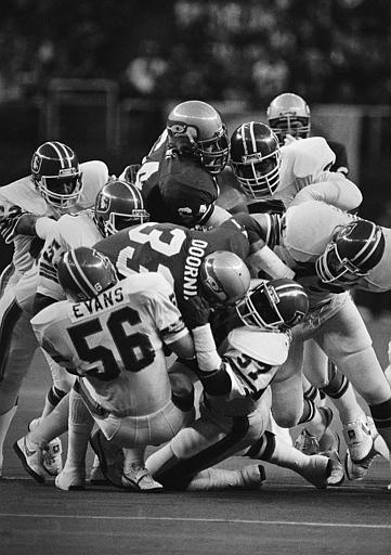 A swarm of Denver Broncos take down Seattle Seahawk's Dan Doornink in the first quarter of a game in the Kingdome in Seattle on Jan. 2, 1982.