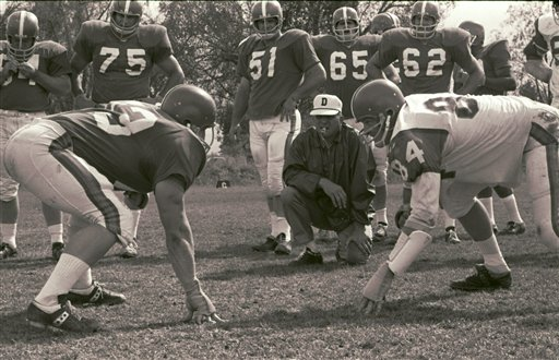 Denver Broncos coach Lou Saban, kneeling, watches as two of his players take a stance during a football practice