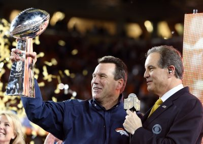 Head coach Gary Kubiak holds up the Lombardi Trophy as he smiles
