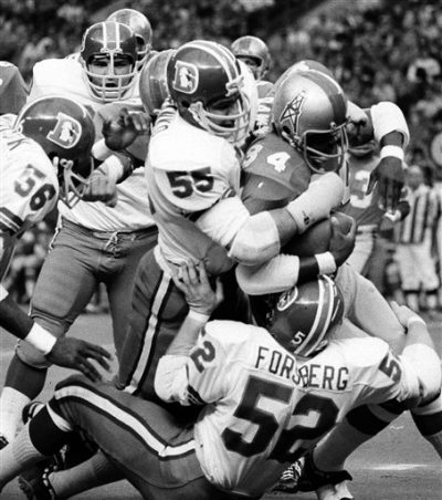 Houston Oilers running back Joe Dawkins (34) is wrapped up by Denver Broncos' Pete Duranko