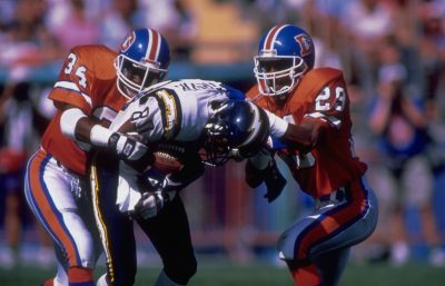 Safety Tyrone Braxton and cornerback Charles Dimry tackle a Charger in a September 13, 1992 win (21-13) over San Diego.
