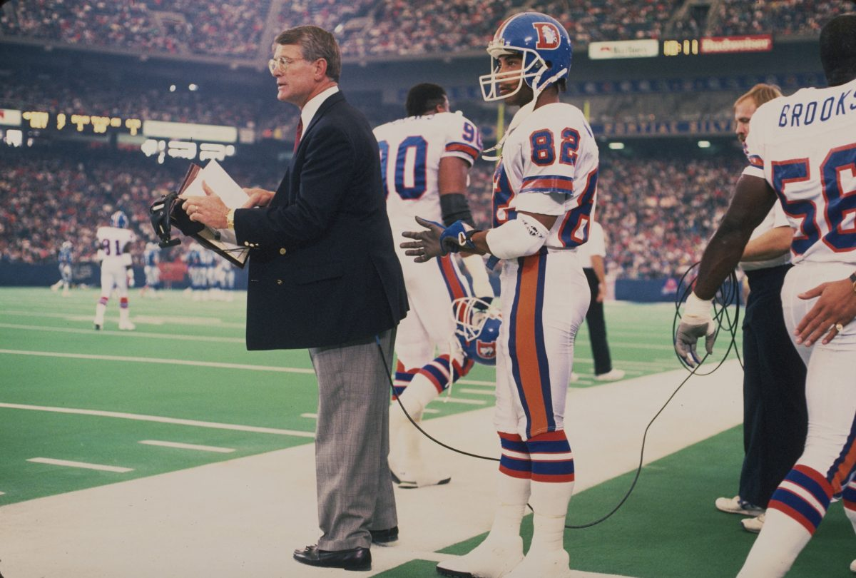 Coach Dan Reeves and receiver Vance Johnson watch from the sideline during a November 22, 1990 loss (27-40) to the Lions in Detroit.