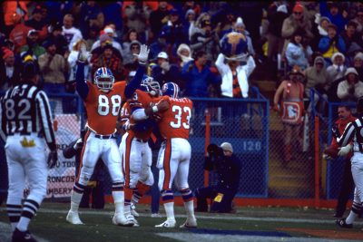 Running backs Tony Dorsett and Sammy Winder celebrate a touchdown with tight end Russell Payne during a November 27, 1988 win (35-24) over the Los Angeles Rams at Mile High Stadium.