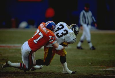 Linebacker Karl Mecklenburg tackles a Steeler ball carrier during a January 7, 1990 playoff win (24-23) over Pittsburgh at Mile High Stadium.