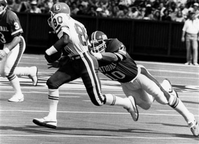 AFC wide receiver Rick Upchurch of the Denver Broncos carries the football on a kickoff return and tries to outrun the reach of NFC linebacker Brad Van Pelt