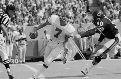 Denver Broncos' John Elway looks back as Chicago Bears' Al Harris closes in on him during second quarter action in Chicago, Oct. 2, 1983